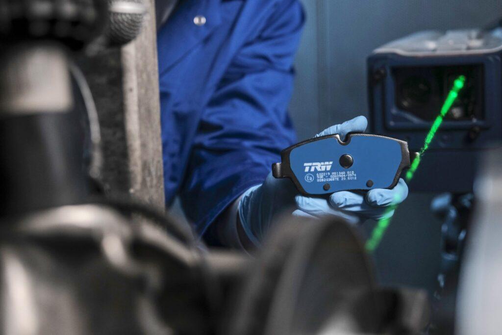 Postać w granatowym uniformie i błękitnej gumowej rękawicy trzyma w ręku hamulec TRW Electric Blue