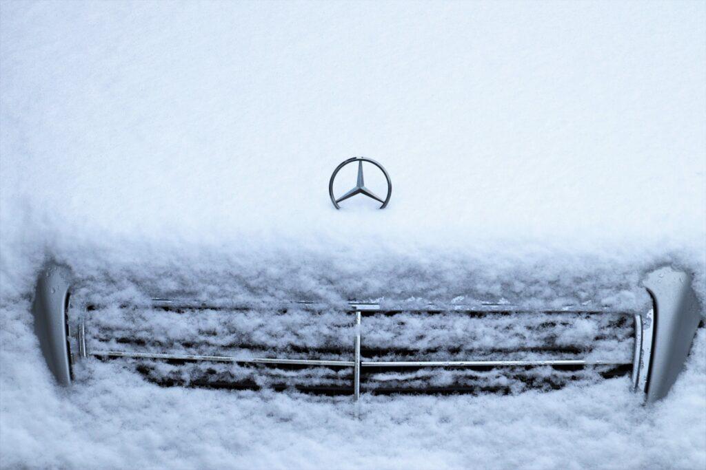 Przednia część auta marki Mercedes schowana pod puszystą warstwą śniegu