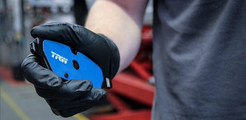 Mężczyzna w czarnej rękawiczce trzyma w ręku niebieski hamulec TRW Electric Blue