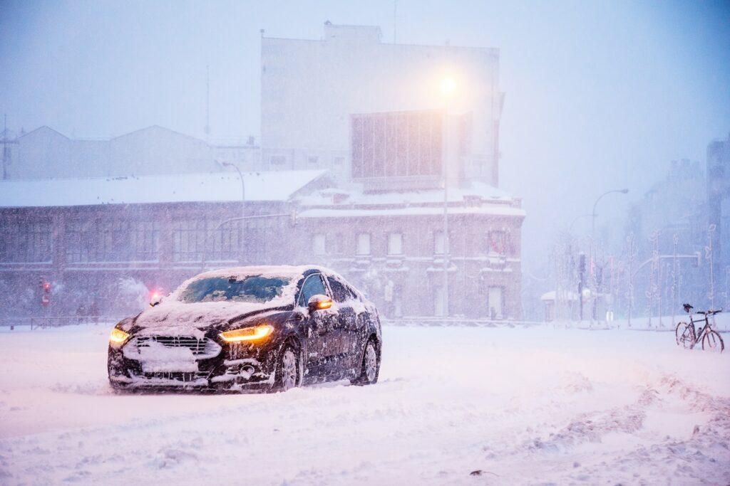 Czarne auto w śnieżnej scenerii, na tle industrialnego budynku