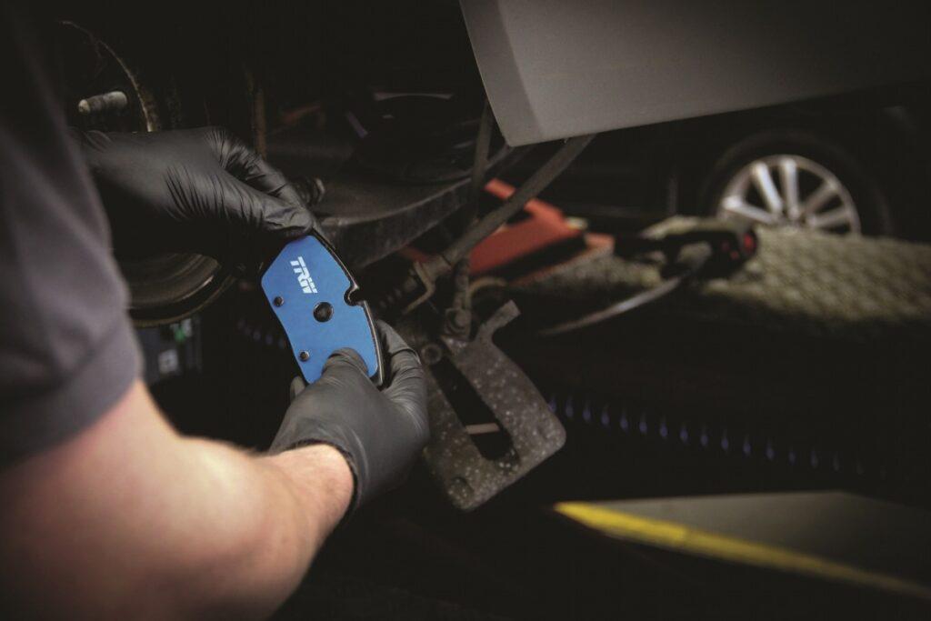 Mężczyzna w czarnych rękawiczkach trzyma oburącz niebieski hamulec TRW Electric Blue
